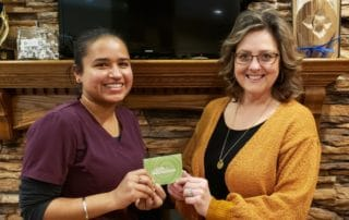 NOVO's dental hygienist presents client with gift card for monthly draw