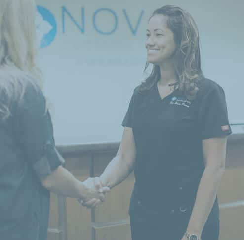 Dr Provo is greeting a client at NOVO Dental Centre Abbotsford under transparent blue overlay
